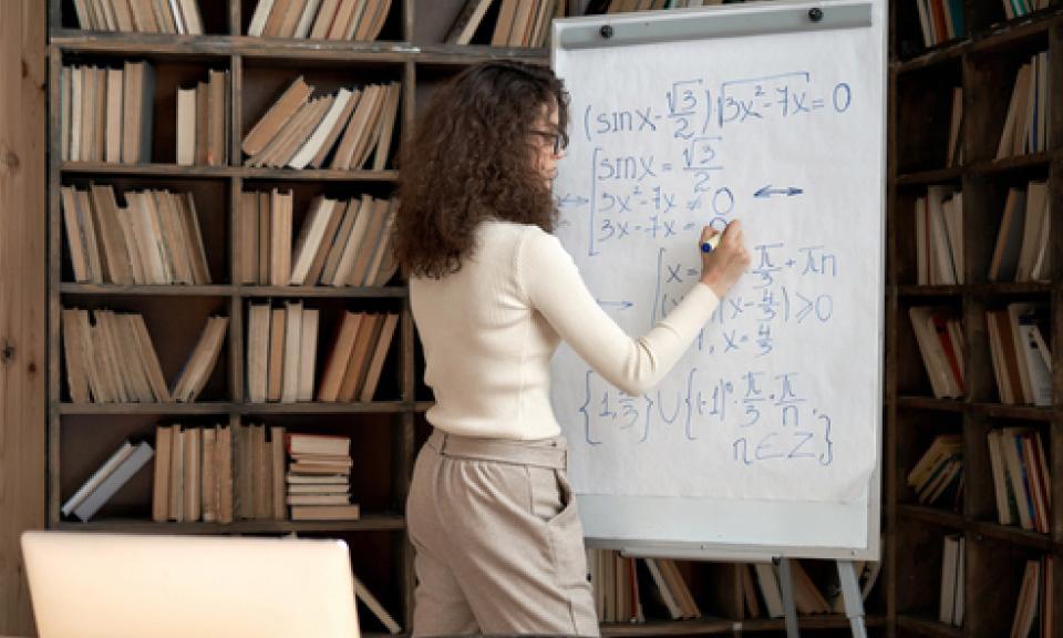 docent-wiskunde-geeft-digitale-instructieles-via-Learnbeat-en-schrijft-wiskundige-vergelijkingen-op-whiteboard